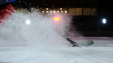 хоккей : Close-up of the puck is on the ice and in slow motion hockey player pulls up and the snow flies into the camera and he takes the puck stick
