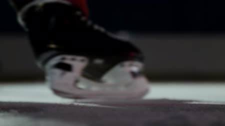 western script : Close-up hockey player strikes the goal in slow motion
