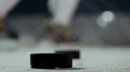 western script : Close-up of the puck on the ice and the hockey player strikes the puck in slow motion