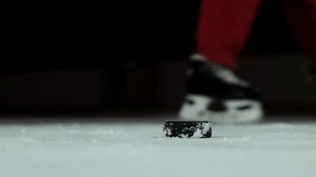 western script : Close-up slow motion hockey puck and flying snow on the ice , hockey player picks up the puck stick
