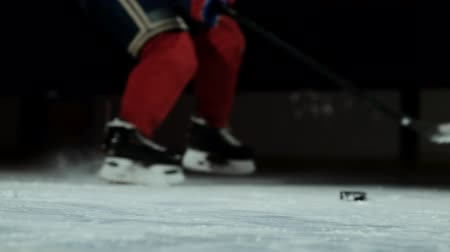 western script : Close-up of the puck is on the ice and in slow motion hockey player pulls up and the snow flies into the camera and he takes the puck stick