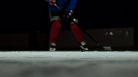 western script : Close-up slow motion hockey puck and flying snow, hockey player picks up the puck stick Stock Footage
