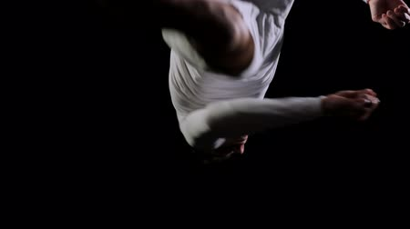 гимнаст : Handsome male gymnast in white clothes on a black background jumping on a trampoline in slow motion performing flips and screws.