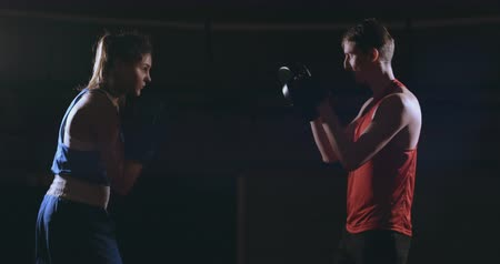 fegyelem : Beautiful brunette boxer working out blows to the paws with a trainer in a dark room