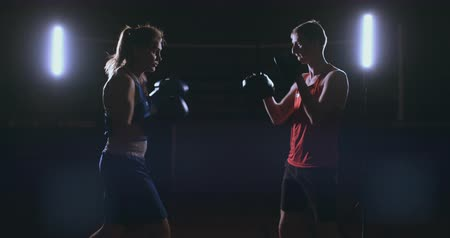 dureza : fitness woman athlete boxing punching focus mitts enjoying intense exercise female fighter training friend in gym workout together slow motion