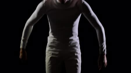 akrobata : A man in white doing acrobatics on a black background in slow motion Stock mozgókép