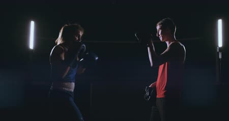 킥복싱 : Female boxer punching a focus mitts with boxing gloves in a smoky gym 무비클립