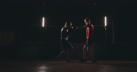 kickbox : Female boxer punching a focus mitts with boxing gloves in a smoky gym Dostupné videozáznamy