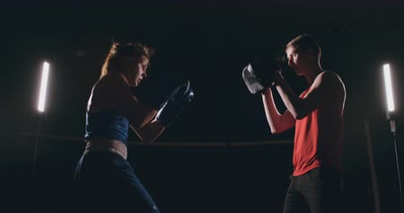 킥복싱 : Beautiful brunette boxer working out blows to the paws with a trainer in a dark room