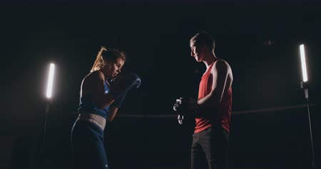 킥복싱 : kickboxer woman athlete kickboxing coach training female fitness friends boxing punching focus mitts enjoying intense exercise workout together in gym close up