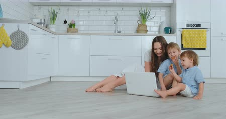 caring : Beautiful modern young family lying on the floor at home and doing something in laptop Stock Footage
