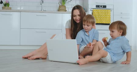 mateřský : Modern apartment mom and two sons sitting on the floor in the living room look at the laptop screen