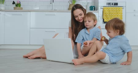 mateřský : Modern technology. Modern apartment loving mom and two small sons sitting on the floor in the living room look at the laptop screen. Children with mom play on a laptop.