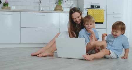 mateřský : Modern apartment loving mom and two small sons sitting on the floor in the living room look at the laptop screen. Children with mom play on a laptop