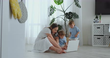 mateřský : Mom with two young children sitting on the floor in a modern apartment in a bright interior with a laptop. Watch the laptop screen and watch family photos. Make online purchases for kids.
