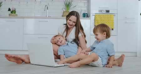 mateřský : Beautiful modern young family lying on the floor at home and doing something in laptop Dostupné videozáznamy