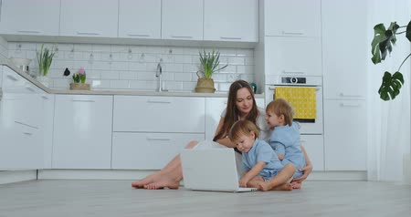 mateřský : A progressive young mother with two young children is talking to her father via video communication. Modern technology is a young family.