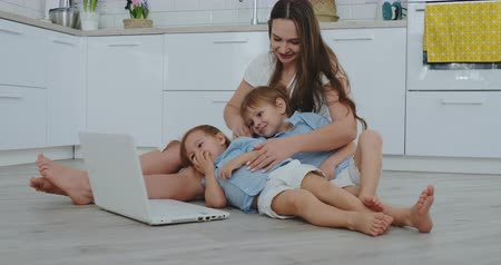заботливый : Mom with two young children sitting on the floor in a modern apartment in a bright interior with a laptop. Watch the laptop screen and watch family photos. Make online purchases for kids.