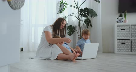 заботливый : A progressive young mother with two young children is talking to her father via video communication. Modern technology is a young family.