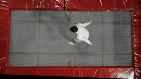 гимнаст : A man in white clothes jumping on a trampoline top view Стоковые видеозаписи