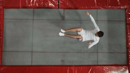 гимнаст : The view from the top gymnast acrobat dressed in white performs a somersault on the trampoline