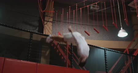 гимнаст : Acrobat gymnast jumping on a trampoline in the trampoline center in white clothes
