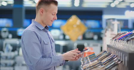 latest : A young handsome man standing at a shop window with smartphones in a portable electronics store chooses to buy a new phone model. Purchase the latest version of the gadget Stock Footage