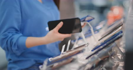 demonstrar : Close-up of a woman in an electronics store holding in her hands two new smartphone and chooses the best one standing near the showcase with gadgets