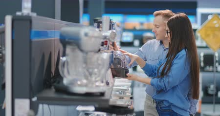 cortes : Young beautiful woman in the appliances store is choosing for its kitchen a blender looking and holding in her hands various models.