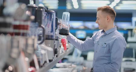 chróm : In the appliances store, a man in a shirt chooses a blender to buy by viewing and holding the device. Dostupné videozáznamy