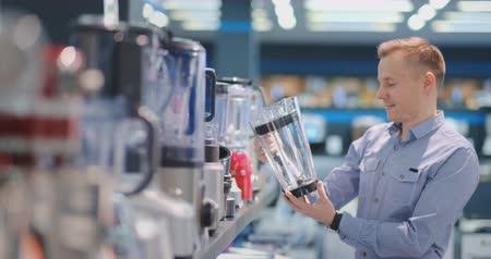 chróm : Young handsome man in appliances store chooses a blender for his kitchen looking and holding various models in his hands