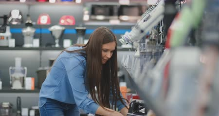 kitchen blender : Young beautiful girl in blue shirt chooses blender in appliances store