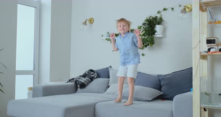 travessura : A 4 years old boy with white hair and a blue shirt jumps and smiles on the sofa. Fun and baby at home. Prank and pampering Vídeos