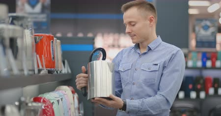 him : Young man chooses electric kettle for his new home in appliances store
