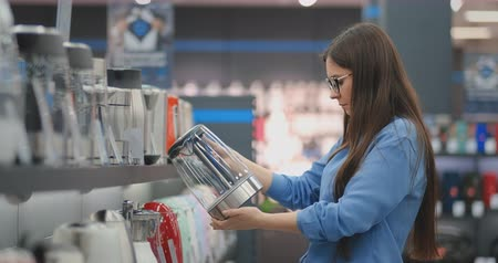 Young beautiful brunette woman chooses an electric kettle to buy. Holds a device in his hands, studies the price tags and the characteristics and design of the model Stok Video