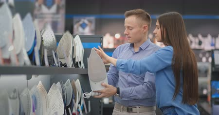 Two young people, a married couple a man and a woman choose a new iron in the household goods store