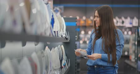 гладильный : A young beautiful woman in a shirt holding the characteristics of the iron studies the prices and chooses to buy an iron in the store standing at the counter