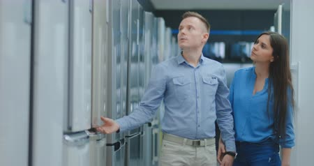 lodówka : A man and a woman open the door of the new refrigerator inspect the design and quality before buying in a consumer electronics store. Read the information on the price tag and characteristics