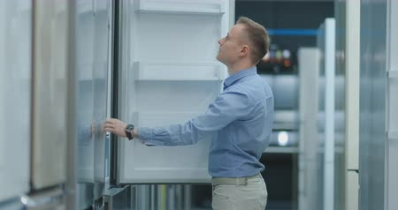 mrazák : A young man in a blue shirt to open the door of the refrigerator in the appliances store and compare with other models to buy the new house