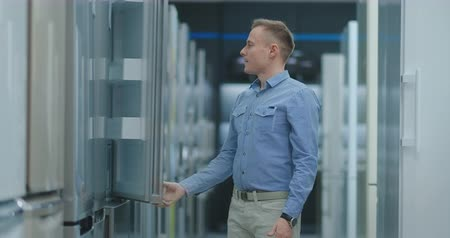 dvojitý : Handsome man in blue shirt open the refrigerator door in appliances store and compare with other models to buy a new home