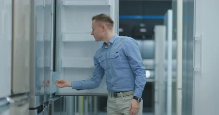 dvojitý : The man open the door of the refrigerator in the appliances store and compare with other models to buy the new house
