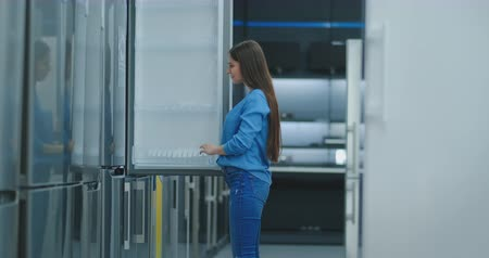 zamrażarka : Young sexy brunette woman in shirt to open the door of the refrigerator in the appliances store and compare with other models to buy the new house
