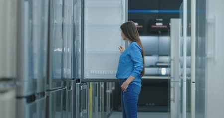 brunette woman in shirt to open the door of the refrigerator in the appliances store and compare with other models to buy the new house