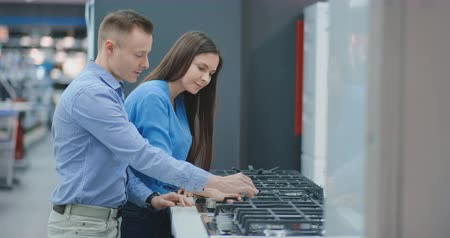 cooktop : Young couple chooses cooktop in store of household appliances