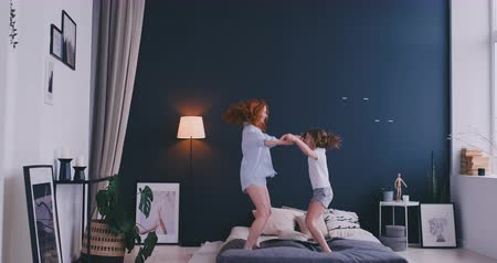 lánya : Beautiful mom and daughter are having fun while jumping on bed at home