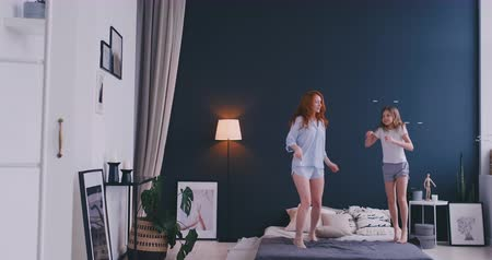 buta : Happy family of cute daughter and young mother jumping and dancing on bed while have fun during morning on holidays at home Stock mozgókép