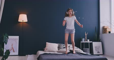 puericultura : Portrait of a little girl listening to the music with the headphones and dancing on her parents bed. Concept: Music, freedom, happiness Stock Footage
