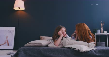 puericultura : Happy loving family. Mother and her daughter child girl playing and hugging on the bed in bedroom.