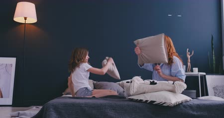 puericultura : Mommy and kid daughter having pillow fight together, young babysitter nanny playing funny game with kid girl at home, happy mother and child enjoy spending time together, family leisure fun activity