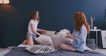 puericultura : Happy family mom baby sitter and little kid daughter having fun pillow fight on bed, young mother nanny laughing playing funny game with small child girl in bedroom joy leisure morning activity